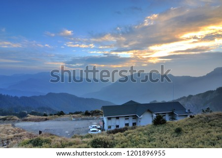 On the high mountains of the continuous mountains, the blue roofs of the white walls of the building, the blue sky has orange clouds. #1201896955