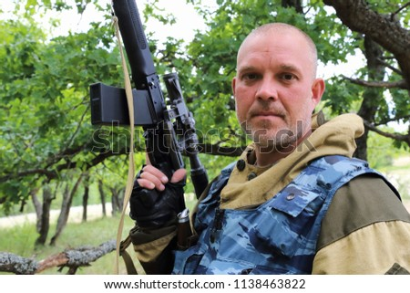 On the hunt. A man of 35-40 years old, a military hunter is standing with a firearm in the forest.