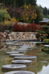On the image is shown a road from stone circles located in a Japanese garden in Crimea. Image with a selective focus