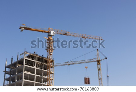 On the image there are two cranes. They ; construct   house.