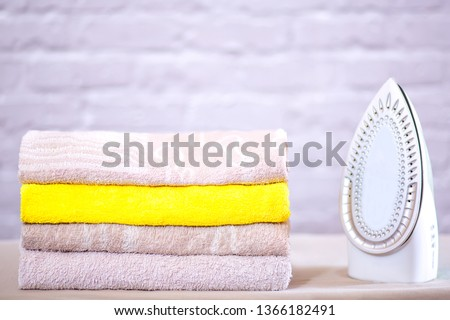 on the ironing board is a pile of ironed towels and an iron #1366182491