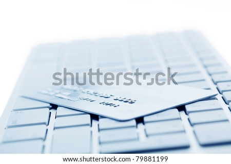 On the keyboard of a computer is a credit card. Online banking and shopping - stock photo