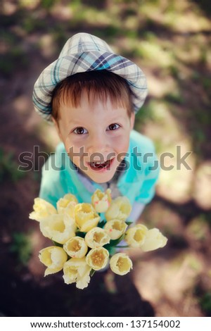 on the nature of the little boy in a blue shirt with a bouquet of white tulips