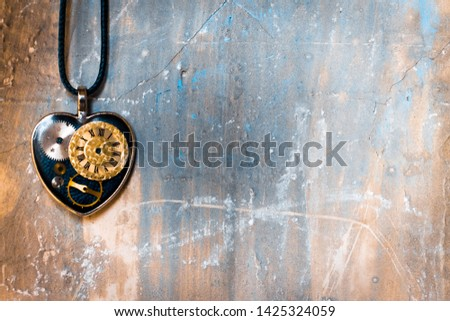 on the old ancient wall there is a pendant in the shape of a heart on a rope, and inside it is an old clock mechanism; concept photo show that eternal love is timeless