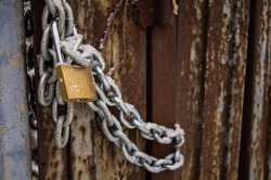 on the old gate with peeling paint hangs a new shiny chain with a lock