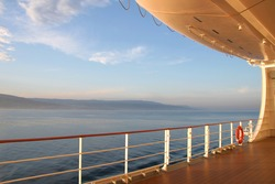 On the open deck of a cruise ship on a calm day, with the coast in the distance.