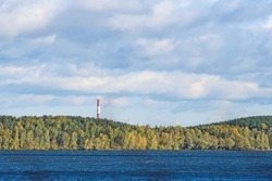On the opposite Bank of the river behind the autumn forest you can see the chimney of a heat and power plant