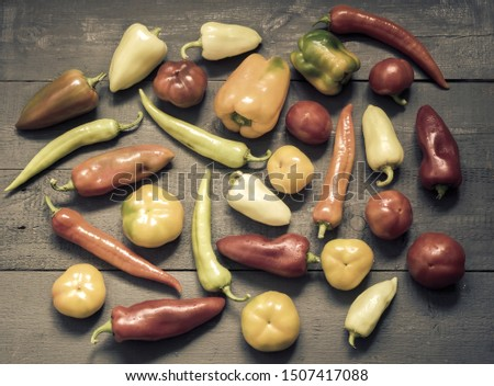 On the painted wooden background of a variety of color and shape of the fruits of bell peppers of different varieties. Top view, negative space.