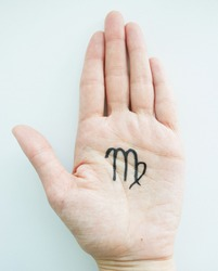 On the palm of a young girl is a top view, with a black felt-tip pen the zodiac sign Virgo is drawn, on a light background. Features, characteristics of the sign of Virgo in the palm of your hand,