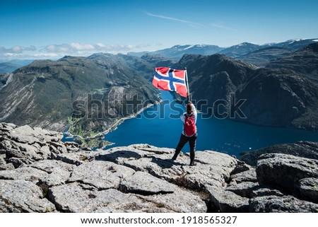 On the peak of scenic Hornelen Europe's Highest Sea Cliff with female model waving a Norwegian Flag