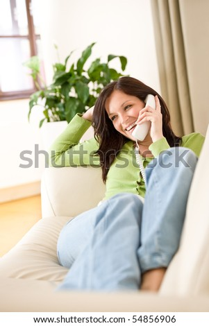 On the phone home: Happy woman calling, plant in background