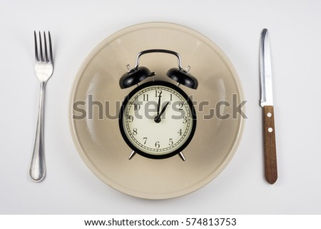 On the plate is an alarm clock, lying next to a knife and fork, white background, top view #574813753