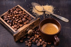 On the raw and dark wooden table, a cup of coffee with a spoonful of brown sugar and roasted coffee beans.