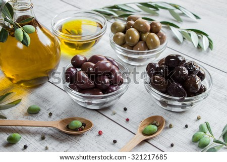 On the right bottle of olive oil to the left 3 bowls with olives, spoons with olives, scattered spices, olive tree branches on wooden white background. 3 different kinds of olives and olive oil.