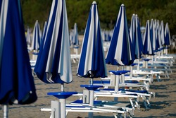 On the sandy beach, the parasols are closed and there are no people on the deck chairs