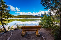 On the shore of lake - comfortable wooden benches. Early morning on cold Pyramid Lake, Jasper National Park