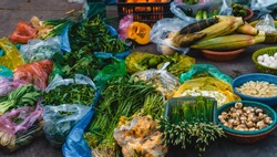 On the sidewalk at a local market in Vietnam, a lot of vegetables at one stand such as eggplant, papaya, lettuce, eggs, bamboo shoots, bitter melon, corn, tomatoes, cucumbers ...