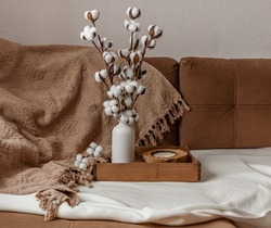 On the sofa is a brown wooden tray, in it a white ceramic vase with cotton flowers, a coconut candle