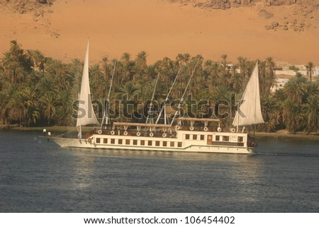 On the southern NIle river south of Cairo Egypt, a fancy tourist boat sails along the sand dunes that line the shore.