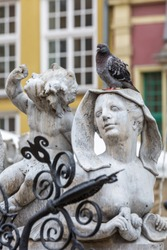 On the square in Gdansk photographed close up a sculpture of a young girl on her head sits a live dove