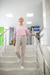 On the stairs. Grey-haired woman in casual clothes going downstairs