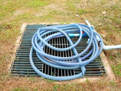 On the steel grating, the drain pipe cover has a rubber hose roll. On the lawn background in the footpath park