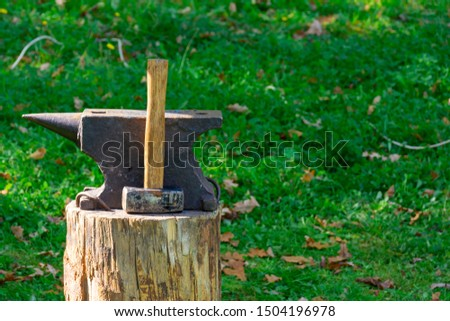 On the stump of a blacksmith's tools: hammer and anvil. The concept of manual labor, craft. Copy space #1504196978