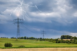 On the sultry, hot summer day, looming storm clouds appear in the sky on the upper Au area near the small town of Trossingen and lightning strikes the high-voltage pylon.