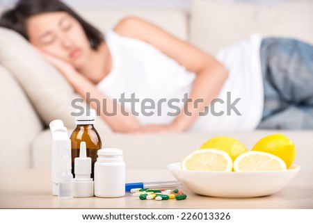 On the table are medicines and lemons. In the background is the asian woman on the bed.