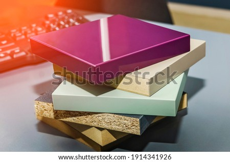 On the table are multi-colored samples of laminated chipboard and MDF finishing materials for the repair and production of furniture. Сток-фото ©