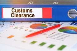 On the table are pie charts, a pen and a folder with the inscription - Customs Clearance. Business and finance concept.