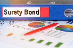 On the table are pie charts, a pen and a folder with the inscription - Surety Bond. Business and finance concept.