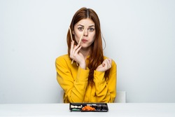 On the table are sushi, woman is eating sushi on isolated background