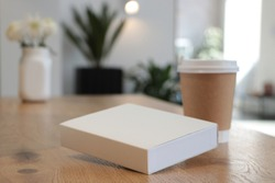 On the table is a mockup of a coffee cup and a white book. Coffee house. Cafe background. Flowers White notepad.