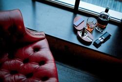 On the table lies a cigar, a lighter, a clock. Cigar scissors. Matches. Smoke from a cigar. Red armchair.