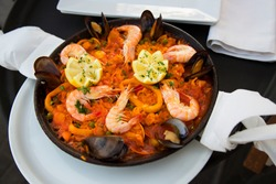 on the table served Paella dish, traditional Spanish oven dish with sea food and rice like shrimp, mussels, mollusks, squid, peas from the pan and with napkins
