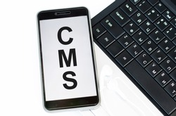 On the table with a laptop lies a phone labeled CMS. It is an acronym for Content Management System.