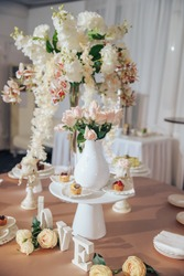 On the table with a pink tablecloth, in a white vase, there are peach and pink roses, and on the table the inscription Love and candlesticks, and another tall thin vase with a large bouquet.