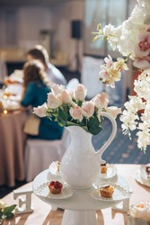 On the table with a pink tablecloth, in a white vase, there are peach and pink roses, and on the table the inscription Love and candlesticks, and another tall thin vase with a large bouquet and cakes.