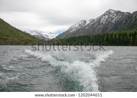 On the water traces from the boat, the landscape of mountains and forests. Best Natural Background