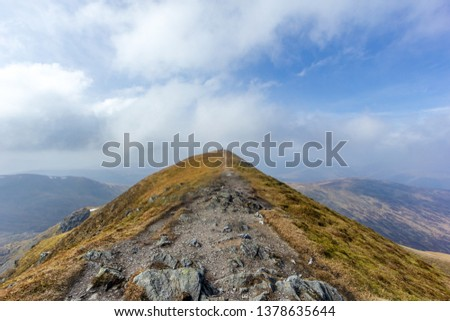 On the way to the summit trig point of a Scottish mountain (Ben Vorlich) with rocky path and dry grass under a majestic blue sky and white cloud #1378635644