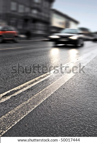 On the wet road with fast approaching cars. Photo with selective focus and shallow depth of field