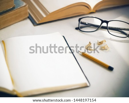 On the white table there are old books, an open diary with a yellow bookmark for notes, shavings from a sharpened, a yellow pencil and glasses in a black frame. Everything is ready for study and work. #1448197154