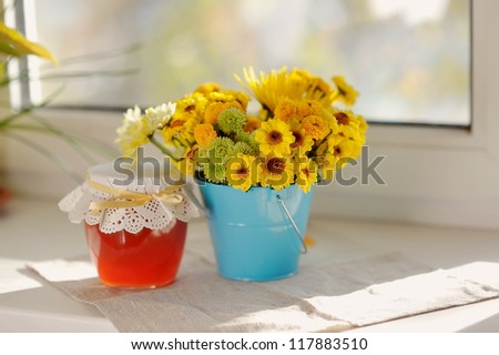 on the window sill in the sun bouquet of yellow flowers and a jar of honey