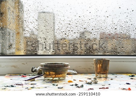 On the windowsill is palette with oil paints and dirty glasses. Rain at the behind the window. water drops against gray spring sky with buildings. focus sat at the bottom.