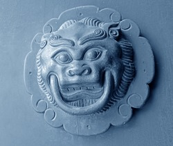On the wooden door knocker in the shape of a lion features