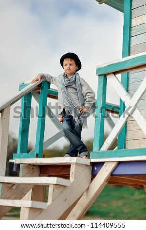 on the wooden stairs is an emotional boy in a black hat with a scarf