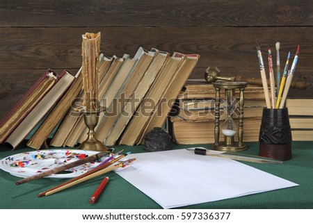 On the wooden table are: old books, a penholder with a feather, white paper, an easel with artist's brushes, a bronze candlestick, a candle and an hourglass. Stylized retro look #597336377