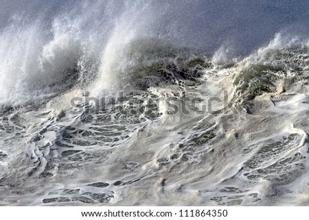 On top of a large and powerful ocean wave in Portugal - stock photo
