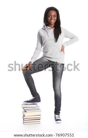 On top of school work. Smiling and relaxed standing pose from beautiful young black teenage student girl, wearing grey hoodie sweater and blue jeans. Girl has one foot on top of a pile of books.